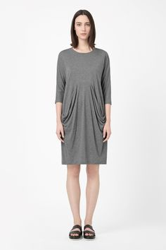 Designed to fall loosely on the body, this casual jersey dress has large draped front pockets. A comfortable relaxed fit, it has ¾ sleeves and a clean round neckline.