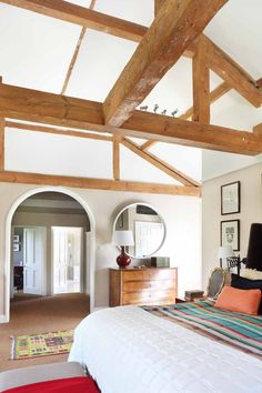 A former horse barn is converted into a stunning English estate, complete with beamed ceilings, wonderfully wallpapered rooms, and colorful style