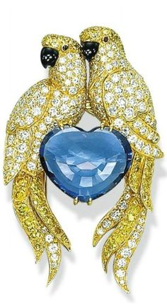 A DIAMOND, COLOURED DIAMOND AND SAPPHIRE BROOCH, BY CARTIER Designed as two lovebirds, each with pavé-set diamond and yellow diamond body, head and tail, ruby eyes and onyx beak, perched on a heart-shaped sapphire, 5.3 cm, with French assay mark for gold Signed Cartier, no. 618231