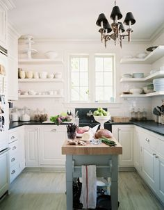 A white kitchen with open shelving and black countertops.