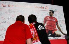 Fans sign a Steven Gerrard board outside the stadium