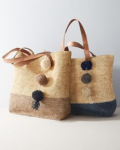 Handmade by local artisans through Fair Trade partnerships, this breezy bag showcases the natural beauty of sustainable raffia with a delicate crochet weave and modern color-block styling. Artfully finished with leather handles and multi-colored raffia pom-poms.