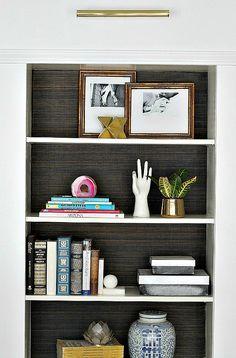 Shelves with grasscloth backing + art lighting. Love.