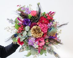 Il bouquet con fiori multicolor e piume di pavone