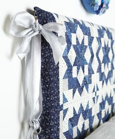 Warm up a headboard by wrapping a quilt over it. To avoid pinning the quilt in place, use small clip-on drapery rings as loops for a festive ribbon-tie closure.