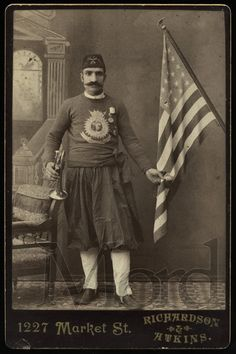 """A very rare, and original, circa 1889 cabinet card portrait of Salvationist """"Joe the Turk"""", born Nashan Garabed to Armenian parents in Turkey. Seen here posed with an American flag and cornet. A rare and striking 124-year-old photograph of the legendary Salvation Army hero! Photographed by Richardson & Atkins, San Francisco."""