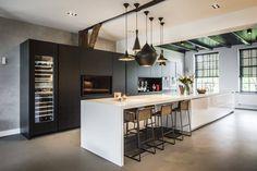 Prachtige landelijk moderne keuken met een antraciete hoge kastenwand en een lang wit kookeiland met daaraan een mooi zitgedeelte. www.demulderkeukensopmaat.nl