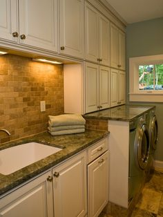 This custom-designed laundry room features a 42-inch high folding station over a front-loading washer and dryer with granite countertops and a marble backsplash.