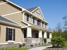 Neutral tan board and batten exterior siding with white corner trim, stone work and board and batten style shutters. Board And Batten Exterior, Board And Batten Shutters, Exterior Siding, Exterior Paint, Vertical Vinyl Siding, Stanton House, Tan House, Steel Siding, Exterior Color Schemes
