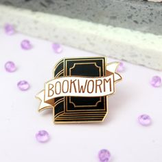 A beautifully detailed Bookworm Enamel Pin. This pin is perfect for booklovers and bibliophiles to declare their love for all things bookish. The pin is gold plated and filled with black and white enamel, then polished to a super shiny finish. All orders will be shipped within 3 days. The important stuff: Handmade in the UK. Measures 3cm by 2.5cm Gold Plated Enamel.