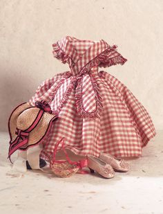Theriault's Antique Doll Auctions, Lot: 50. French Dress with Bonnet and Slippers for 1860 Era, Of silk/cotton two-tone sienna and cream checkered pattern, the dress features a low rounded neckline criss- crossed by a fringe-edged collar that terminates in lappets that fall below the fitted waist. The box-pleated sleevelets are fringe-edged. The waist is fitted with an invisible set-in band, above tiny cartridge pleats. #dollshopsunited