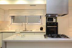Cocina de muebles de pvc blancos con mesadas de silestone. Isla con anafe y campana. Sobremesada revestido en silestone.