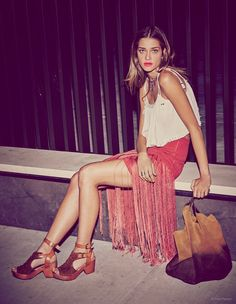 """Ana Beatriz Barros poses in a fringed skirt and white top for """"Havana Nights"""" feature."""