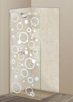 Shower Divider Panel featuring the Circularity design in the 1D Positive Clear effect by Sans Soucie Art Glass. Design elements are sandblast etched on the top surface of smooth, clear glass, and are solid white shapes.  This effect is considered semi-private, as the clear glass background area of the glass, will vary by design.