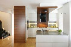W półotwartej kuchni dominują biel i drewno w ciepłym wybarwieniu orzecha. jasnoszare elementy wystroju, takie jak blaty oraz szkło nad nimi tworzą eleganckie tło dla tej aranżacji. Projekt Kamila Paszkiewicz. Fot. Bartosz Jarosz.