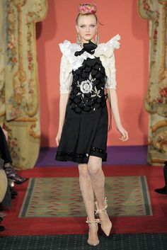 "Sweet black dress with sequin embellishments and embroidered white rose. The little white shrug top with lacy fanning collar makes the rose ""pop."" From Christian Lacroix Spring 2009 Couture."