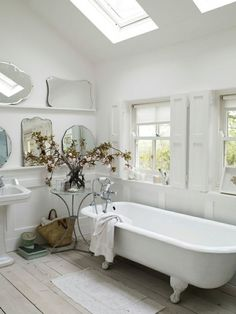 Mirrors, mirrors on the wall... a beautiful bathroom, clawfoot tub, skylights, and white.