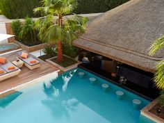 Customized Outdoor Living Spaces with poolbar, deck, & thatched roof | Cape Reed