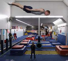 U.S. trampoline gymnast Michael Devine trains for the London 2012 Olympics at his home gym, the J and J Tumbling and Trampoline Team Center, while his coach Shaun Kempton (bottom) looks on in Pecatonica, Illinois, May 7, 2012.