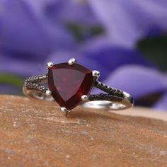 Celebrate your special moments of life while wearing this blazing red quartz and black diamond ring. This beauty features trillion-cut deep red charm, highlighted by ravishing sparks of black diamond on the shanks in nickel free sterling silver with platinum overlay. Distinctive and unique, this beauty is designed to add a dazzling appeal to your persona. Free Shipping Gift Box