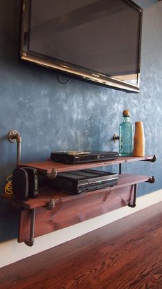 industrial living room shelf - clever to have the vertical board to cover wires