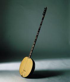 TAMBUR Irán, Irak, Kurdistán, etc. También se le conoce como tanbur kebir turkí.. El trasteado del instrumento, que cuenta con cuartos de tono, se realizaba originalmente con cuerdas de tripa.Habitualmente se toca con una púa muy gruesa, fabricada en hueso, y de forma excepcional se toca con arco, colocándose verticalmente sobre una pierna.