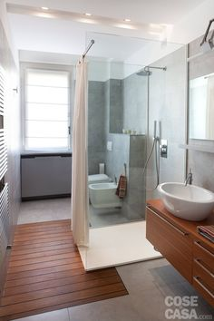 Il #bagno viene idealmente suddiviso in tre posizionando il box doccia nel mezzo. Come nella zona giorno, anche qui un controsoffitto, che riproporziona il volume abbassandone l'altezza da 300 a 240 cm, individua le aree funzionali con l'ausilio di luci differenti. Davanti alla doccia, l'inserimento di parquet nel pavimento in gres raccorda l'area lavabo e quella dei sanitari