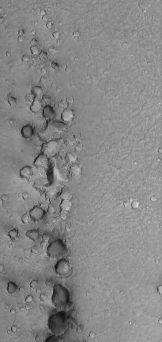 Battered Martian Craters August 6, 2013 This Mars Global Surveyor (MGS) Mars Orbiter Camera (MOC) image shows a chain of clustered and battered craters. These formed by secondary impact. That is, somewhere to the south (beyond the bottom of this image)