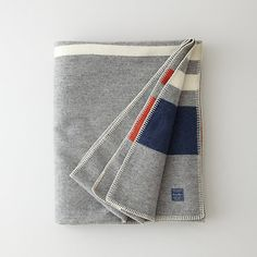 "Soft, military inspired wool blanket with blue / orange / white stripe end details. ""This cozy Steven Alan collab blanket is toasty and chic."