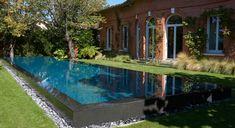 Une piscine miroir paysagée à l'arrière d'une demeure traditionnelle toulousaine | Piscines Carré Bleu