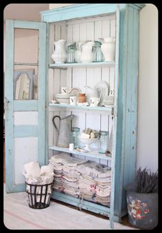rustic old armoire filled with treasure--look at the stacks of old feedsacks and French toweling