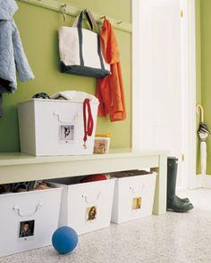 Opbergruimte voor de hal met losse manden. Slim gemaakt plekje in de hal waar je snel alle losse spullen zoals jassen, sjaals en handschoenen kwijt kunt. Iedereen krijgt een eigen mand met zijn of haar foto erop zodat je in 1 oogopslag ziet wat van wie is. Door de kapstok in dezelfde kleur als de muur te schilderen valt hij minder op.