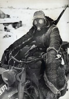 Riding on an exposed vehicle in the Russian Winter, here a combination motorcycle, required protective clothing. This Kradfahrer wears a sentry's fur-lined overcoat, heavy mittens, the fur-lined cap of the reversible winter suit, which is no doubt being worn beneath the overcoat, and a gasmask for face protection. The air filter canister has been removed from the gasmask 38. Special extra eyepiece lens were issued for cold weather to prevent fogging by creating an airspace between the two…