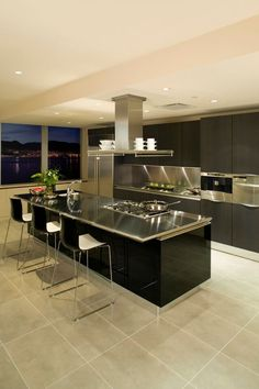 This sleek black kitchen is fresh and modern. A chrome countertop sits upon the island, which features a sink, stove, and eat-in extension.