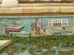 """""""LA PESCA"""". Mosaico rectangular en tesela cerámica modelado, en relieve,  por Paco Presa Merodio (Torrelavega, 1961 -). Instalado en 2007, fue realizado  en pasta de loza y arcilla roja y decorado con esmaltes y engobes coloreados, cocidos a 1050-1100º C. Se evoca la actividad económica tradicional de Santurtzi, la pesca: una bonitera faenando en alta mar; una vista del puerto pesquero, presidido por el edificio de la Cofradía y un grupo de pescadores pertrechados dirigiéndose a faenar."""