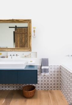 Gorgeous bathroom with half tiled wall and gold mirror and blue floating vanity