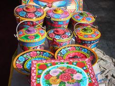 'Truck art' style on tin utensils at Lok Virsa Mela, Islamabad, PAKISTAN. Lok Virsa Mela is a folk heritage annual event in Spring season in Islamabad, where craftsmen and craftswomen from all provinces of Pakistan gather and display their work and sell their handcrafted artwork of all kinds. There is a 'Artisans at work' segment where artisans show how they produce an artwork.  Photography: Zehra Naqavi(Architect/artist).  April 14, 2012. All photographs are watermarked.