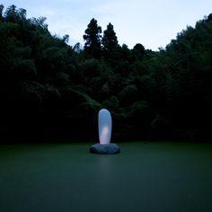 """森まりこ  トムナフーリ  竹林に囲まれた小道を登ると、池の中央に生と死を象徴する現代のモニュメントが出現。この立体は神岡宇宙素粒子研究施設(スーパーカミオカンデ)とコンピュータで接続しており、超新星爆発(星の死)が起こると光を放つ。  →sculptureとメディアアート?の関連性を教えてくれた。見た目だけが美しいという表面的な光のアートはどうかなーっておもってたし、それ以上の意味を含めた作品はできないものか考えていたときにこの作品に出会った。今まで光だけで何を表現できるかわからなかったけど、光という""""material""""を通して中継的な生死を表現することに感銘を受けた"""