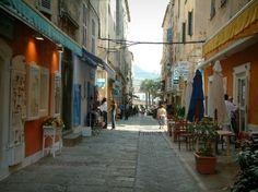 LÎle-Rousse: Rue bordée de maisons avec boutiques et terrasse de café - France-Voyage.com