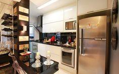Para dar um pouco de amplitude à cozinha de 6 m2, a arquiteta Cilene Monteiro Lupi abriu uma meia cozinha americana, em frente à geladeira. Foto: Divulgação