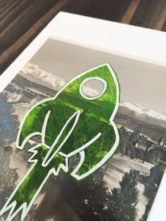 Blastoff! This is a retro green rocketship illustration on top of a real photo vintage postcard of the Alps mountains and mounted on paper.