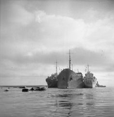 The damaged tanker OHIO, supported by Royal Navy destroyers HMS PENN (left) and HMS LEDBURY (right), approaches Malta after an epic voyage across the Mediterranean as part of convoy WS21S (Operation Pedestal) to deliver fuel and other vital supplies to the besieged island. OHIO's back was broken and her engines failed during earlier German and Italian attacks.