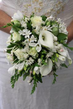 white calla lilies, freesias, stephanotis, hyacinth,roses. grannie grows stephanotis.