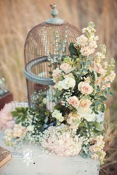 birdcage overflows with a gorgeous flower arrangement for rustic wedding