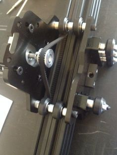 OX CNC and the Everman drive system. First, applying double-sided tape to the GT3 timing belt. Then securing the belt in the v-slot. 2nd drive belt under the wheels and over the pulley. Keeping top belt taught and sliding gantry onto the v-slot. 3d printed v-slot connector. Note the 3d printed v-slot connector holding the two 2060 rails together.