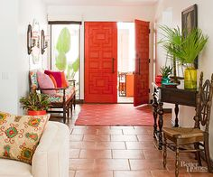 Want to go bold in a big way? Paint your entry doors a fiery hue that demands attention. Impressive on their own, these carved doors make a colorful statement, inspiring the orange, aqua, pink, and red hues popping up as fabrics in the foyer and the adjacent seating area. The neutral walls, flooring, and furniture provide calming counterpoints that keep the clamorous tones in check./