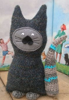 This is my version of the cheshire cat....He is made from soft wool tweed fabric, with hand crocheted stripey tail and paws.  He wishes he could fly a
