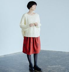 赤のスカートをポイントにまとめたリラックスコーディネート。大きめのニットを合わせてゆったりと。