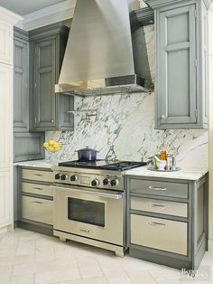 Stainless-steel cabinet drawers add an unexpected contemporary touch to a primarily traditional kitchen. The drawers duplicate the range and hood's shimmer, standout from gray cabinet frames, and sleekly contrast with molding-trimmed upper cabinets.