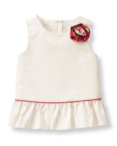 Crafted in cotton chintz sateen, our pretty top is detailed with a silk plaid rosette. Peplum ruffle and piping complete the piece.